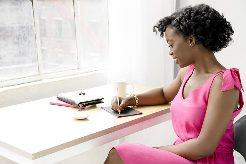 Styled Stock Photo Woman of Color writing at desk